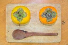 Persimmon δύο και ξύλινο κουτάλι στον τεμαχίζοντας φραγμό Στοκ Εικόνες