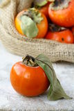 Persimmon. On a wooden table with a bag in the background royalty free stock images