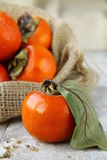Persimmon. On a wooden table with a bag in the background Stock Photography