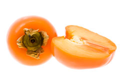 Persimmon. The persimmon cut half lying near to whole (isolated, focus on the cut half Stock Images