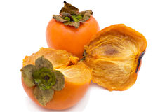Persimmon. Fruits whole also it is pulled down �� on a white background Stock Images