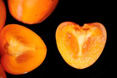 Persimmon on a black background royalty free stock photography