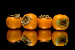 Persimmon on black background with reflection Royalty Free Stock Photos