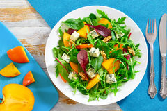 Persimmon, blue cheese, spinach, arugula, lettuce leaves and wal Stock Photo
