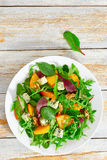 Persimmon, blue cheese, spinach, arugula, lettuce leaves and wal Stock Photography