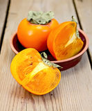 Persimmon on the board in pottery Royalty Free Stock Photography