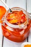 Persimmon dżem w szklanym słoju na drewnianym tle zdjęcie stock