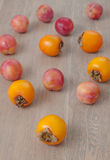 Persimmon fruit and pink plums. On the wooden background royalty free stock images
