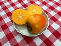 Persimmon fruit. In a white dish displayed on a red and white gingham tablecloth. The fruit has been cut open to show the pattern of the flesh inside Royalty Free Stock Photos