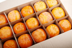 Persimmon fruits. Ripe persimmon fruits in a box Royalty Free Stock Photo