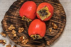 Persimmon fruits in basket and persimmon colored leaves on wooden background, top view royalty free stock photos