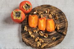 Persimmon fruits in basket and persimmon colored leaves on wooden background, top view. Nhealthy food stock photography