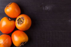 Persimmon fruits on black wood Royalty Free Stock Photos