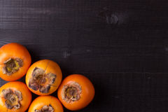 Persimmon fruits on black wood Stock Photo