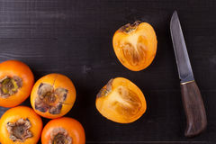 Persimmon fruits on black wood Stock Image
