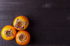 Persimmon fruits on black wood Royalty Free Stock Photo