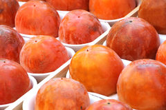 Persimmon fruits at the market, detailed view. A detailed view of some persimmon fruit, at the market, landscape cut Stock Photo