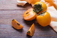 Persimmon fruits on the wooden table Royalty Free Stock Images