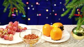 Persimmon, grapes and Nuts with honey and are on the table with a decorated Christmas tree and flashing gerunds blurred bokeh. Photographed with dolly from stock video footage