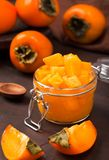 Persimmon jam or marmalade in beautiful glass jar with fresh ripe fruits stock images
