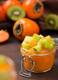 Persimmon jam or marmalade in glass jar with cubes of kiwi and persimmon royalty free stock images