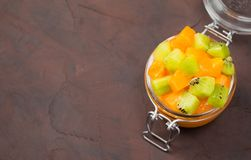 Persimmon jam or marmalade in glass jar with pieces of kiwi and persimmon on brown background stock photo