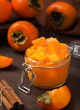 Persimmon jam or marmalade in glass jar with powdered cinnamon falling down stock photo