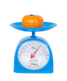 Persimmon on kitchen scale isolated on white background Stock Photography