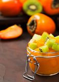 Persimmon and kiwi jam in beautiful glass jar with fresh cut fruits on brown background stock photo