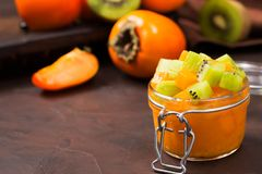 Persimmon and kiwi jam in beautiful glass jar with fresh cut orange and green fruits stock photography