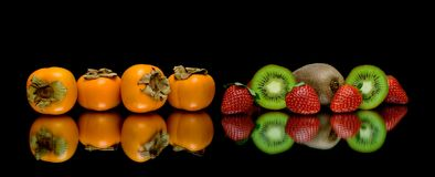 Persimmon, kiwi and strawberries on a black background Stock Photography