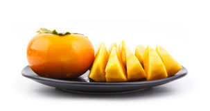 Persimmon. Many pieces of fresh persimmon on dish Stock Photo