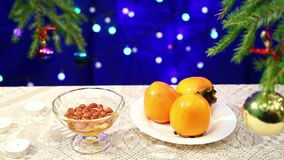 Persimmon, nuts with honey and are on the table with a decorated Christmas tree and flashing gerunds blurry bokeh. Photographed with dolly from right to left stock video