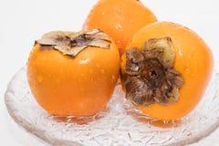 Persimmon owoc na szklanym talerzu obrazy stock