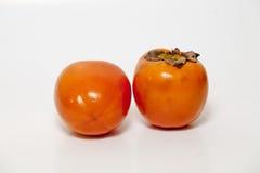 Persimmon på vitbakgrund Arkivfoto