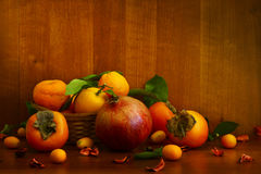 Persimmon, pomegranate and citrus fruits. Persimmon, pomegranate and citrus on textural background Royalty Free Stock Photos