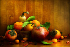 Persimmon, pomegranate and citrus fruits. Persimmon, pomegranate and citrus on textural background Stock Images