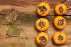 Persimmon resting on an old table Stock Image