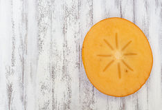 Persimmon slice. Overhead view on a white wooden kitchen table Royalty Free Stock Photo