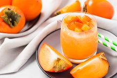 Persimmon smoothie or jam in beautiful glass jar with fresh ripe whole and cut fruits and straws on gray background. stock photo