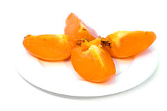 Persimmon on white plate. Isolated Stock Photos