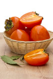 Persimmon in a wicker bowl Stock Images