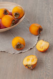 Persimmon on wooden background. Persimmon fruit cut in half and plate of kaki fruit royalty free stock photo