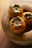 Persimmon In Wooden Bowl Stock Photos