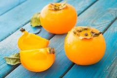 Persimmons γλυκών πορτοκαλιών με τα πράσινα φύλλα Στοκ φωτογραφία με δικαίωμα ελεύθερης χρήσης