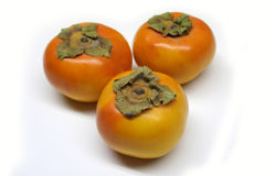 Persimmons. Three persimmons on white background Stock Images
