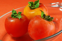 Persimmons at angle. Persimmons in glass dish, colorful, close up Stock Images