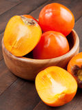 Persimmons in bowl on wooden table Stock Photography