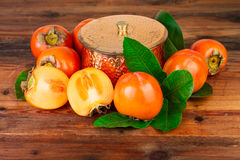 Persimmons with copper vase on old wood. Oriental East still life Stock Photo