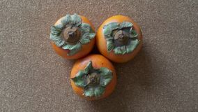 Persimmons on a Cork background Royalty Free Stock Photos